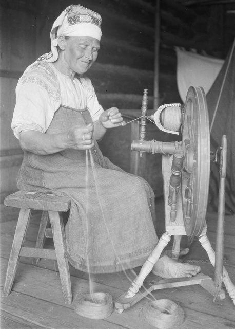 Kehräävä inkeroisnainen on pukeutunut kirjontakoristeiseen paitaan, siniseen olkainhameeseen ja päähän on sidottu sapana-päähine. Kuva A.O. Väisänen 1914. Museovirasto.