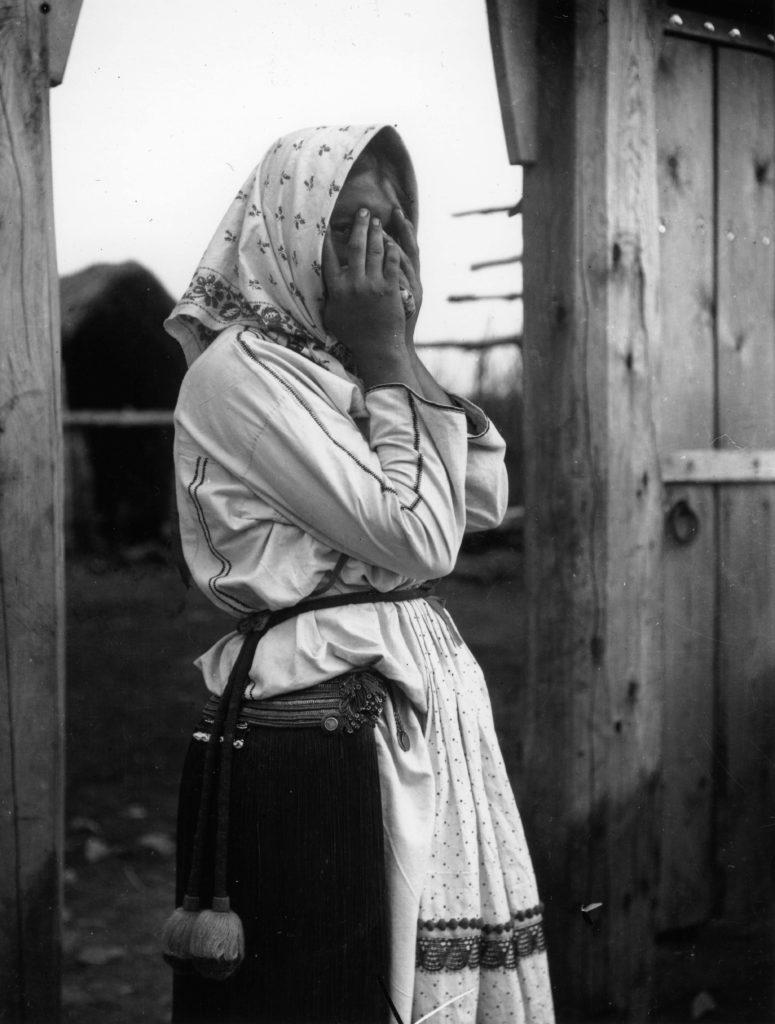 Ersämordvalainen tyttö ujostelee kuvausta. Mekon lisäksi tytön vyötäröllä on tuuheista hapsuista koottu vyönkoriste. Kuva A. O. Väisänen 1913. Museovirasto.