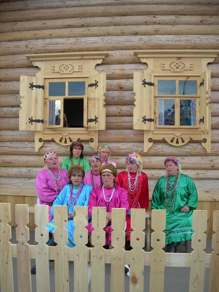 Mokšamordvalaisia naisia museokylässä kesällä 2008. Pukuun kuuluu valkoisen mekon lisäksi hihallinen esiliina, joka ommellaan värikkäästä kankaasta. Kuva Ildikó Lehtinen.