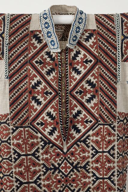 Yksityiskohta hantinaisen kirjontakoristeisesta paidasta. Hantinkielisen alueen eteläosissa Kondajoella pella- tai nokkoskankaisia paitoja koristeltiin villalankakirjonna 1800-luvun puolivälissä. Teeri-kuviot olivat suosittuja aiheita kirjonnassa ja myös tuohiesineiden koristelussa. Suomen kansallismuseo.