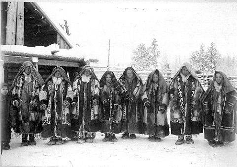 Poroturkkiin pukeutuneita mansinaisia. Edestä avonaisissa turkeissa on mosaiikkikoristelua. Asuun kuului suurkokoinen hapsureunainen huivi. Kuva Artturi Kannisto 1906. Museovirasto.